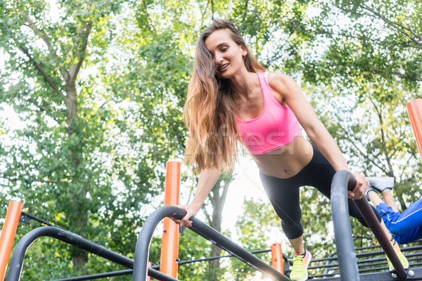 Low-angle view of a fit woman smiling while exercising single-ar Stock photo © Kzenon