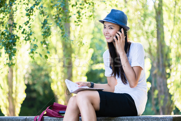 Asian woman talking on mobile phone outdoors Stock photo © Kzenon