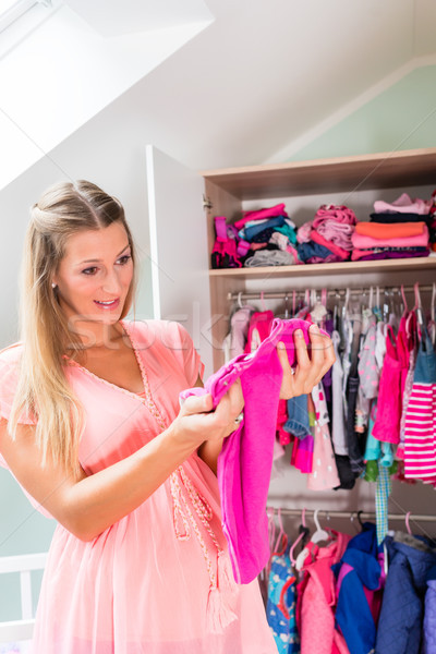 Pregnant woman in front of wardrobe in childs room Stock photo © Kzenon