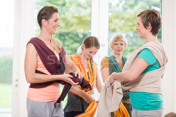 Stock photo: Young women learn how to use baby carriers for carrying children