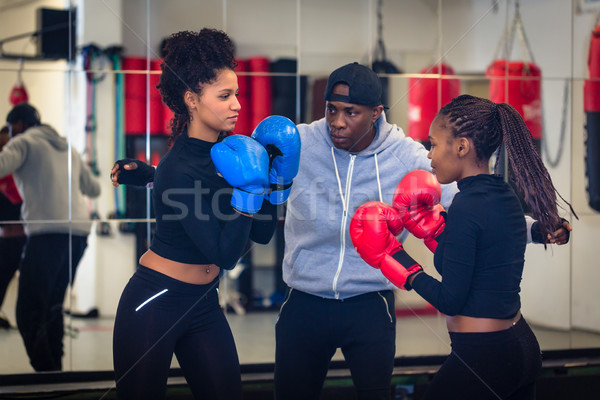 Experienced boxing trainer supervising and teaching two female boxers Stock photo © Kzenon