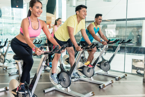 Fit women burning calories during indoor cycling class in a fitness club Stock photo © Kzenon