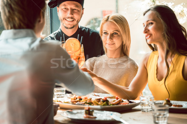 Experienced chef congratulated by four people at a trendy restaurant Stock photo © Kzenon