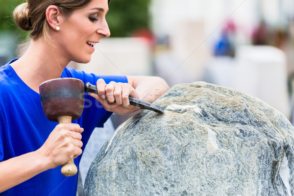 Stonemason working on boulder with sledgehammer and iron Stock photo © Kzenon