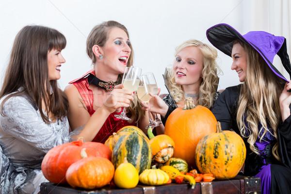 Four cheerful women celebrating Halloween together Stock photo © Kzenon