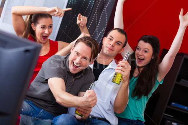 Stock photo: Friends watching exciting game at TV