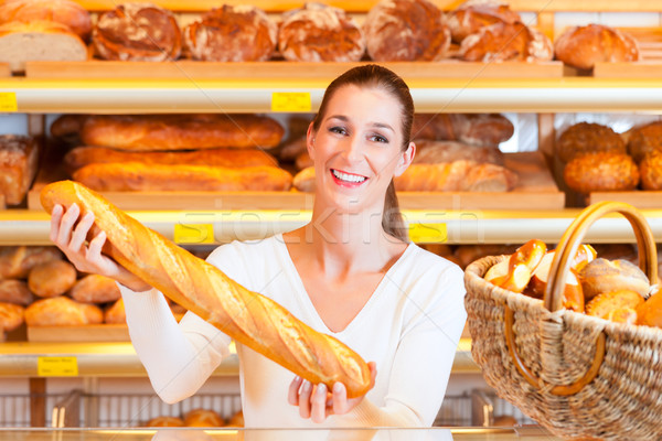 Female baker in her bakery with baguette Stock photo © Kzenon