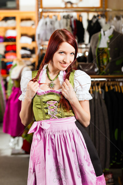 Woman is trying Tracht or dirndl in a shop Stock photo © Kzenon