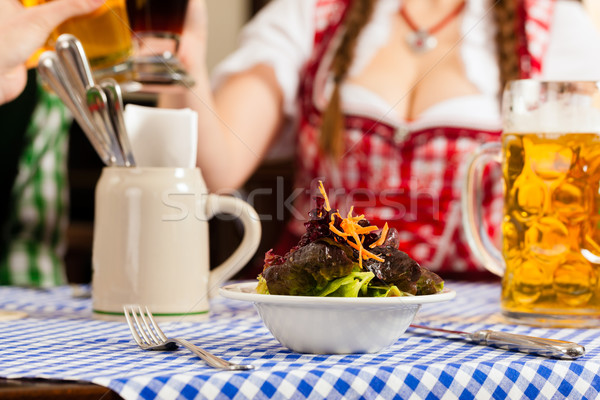 People in traditional Bavarian Tracht eating in restaurant or pub Stock photo © Kzenon