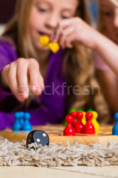 Család játszik társasjáték otthon kettő nővérek Stock fotó © Kzenon