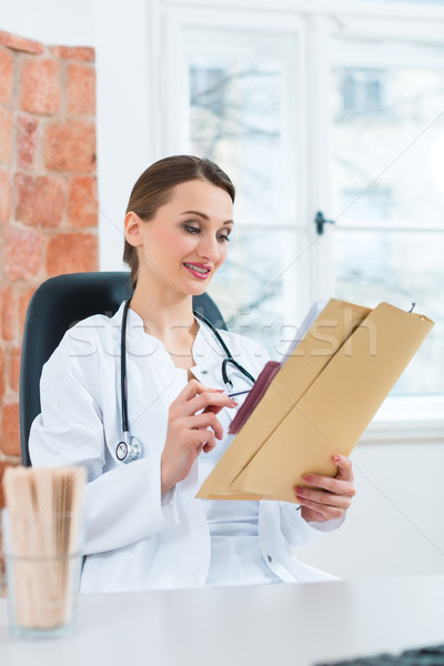 Female doctor reading in document Stock photo © Kzenon
