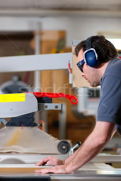 Carpenter using electric saw Stock photo © Kzenon