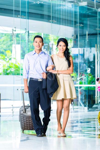 ázsiai pár sétál hotel lobbi bőrönd Stock fotó © Kzenon