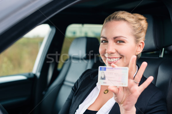 Woman showing her driving license out of car Stock photo © Kzenon