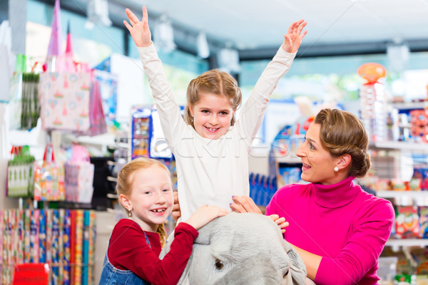Little child riding on stuffed animal in toy store Stock photo © Kzenon