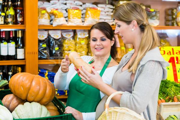 Woman buying pumpkin and vegetables in delicatessen Stock photo © Kzenon