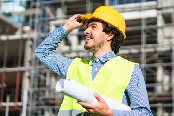 Architect studying floor plan at construction site Stock photo © Kzenon