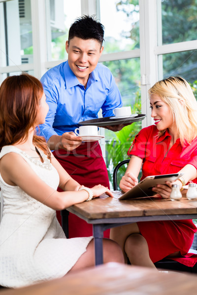 Stock photo: Waiter serving two ladies coffee in a restaurant