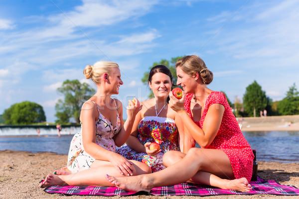 Nő eszik gyümölcs folyó tengerpart piknik Stock fotó © Kzenon