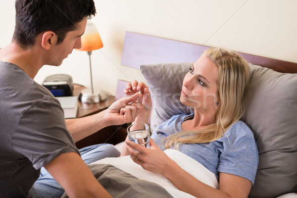 Young caring man giving pill to his sick partner Stock photo © Kzenon