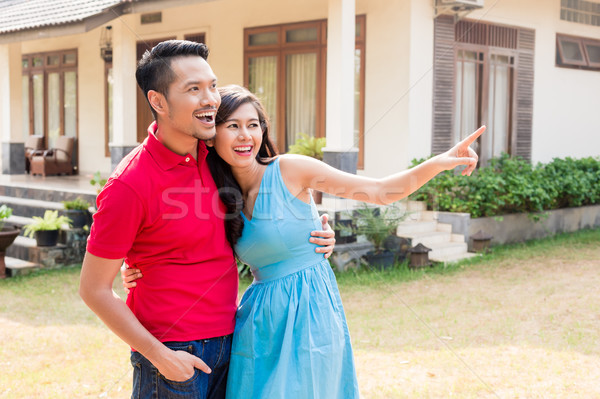 Cheerful young couple looking in the same direction in front of  Stock photo © Kzenon