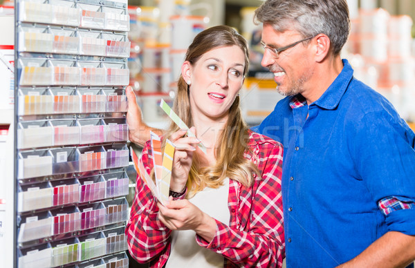 Couple choosing color of paint in hardware store Stock photo © Kzenon