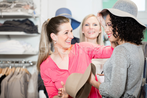 Girlfriends on shopping spree trying ladies hats and other fashi Stock photo © Kzenon