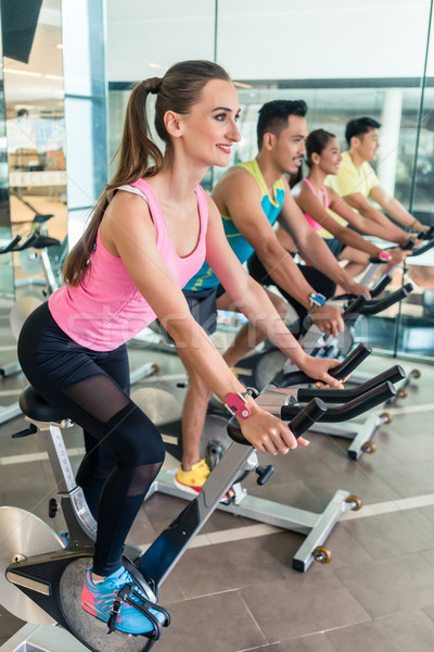 Beautiful fit woman smiling during cardio workout at indoor cycling cla Stock photo © Kzenon
