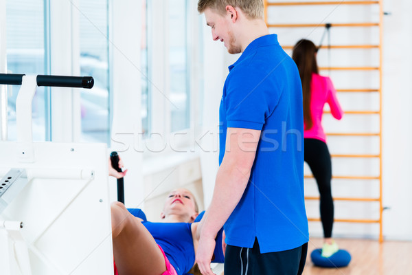 Men and women doing workout on diverse equipment in gym Stock photo © Kzenon