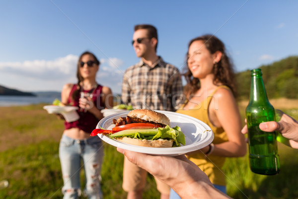 Young people on barbecue party, burger and beer Stock photo © Kzenon