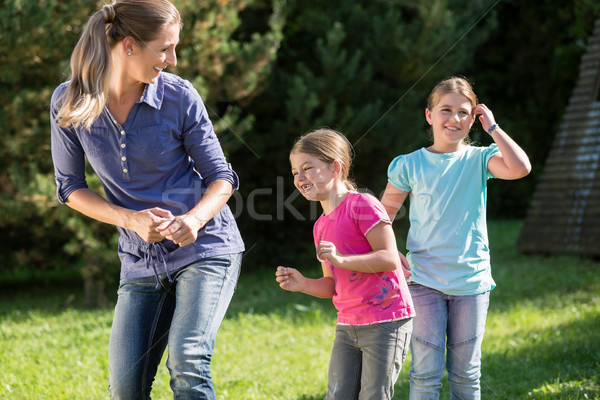 Mother with daughters doing dance exercise outdoors Stock photo © Kzenon