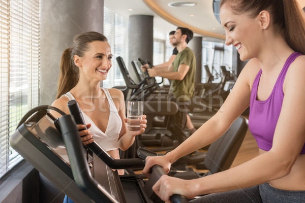 Young woman helping her friend to set the parameters of treadmill Stock photo © Kzenon