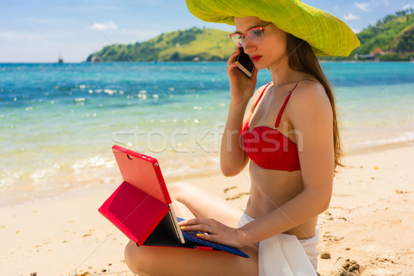Young woman talking on mobile phone while using a tablet on the beach Stock photo © Kzenon