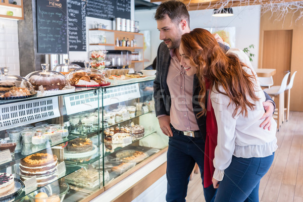 Beautiful woman choosing a delicious cake while standing next to her boyfriend Stock photo © Kzenon