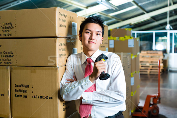 Young Man in a warehouse with Scanner Stock photo © Kzenon