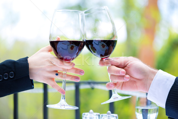Stock photo: Hands holding red wine glasses to clink