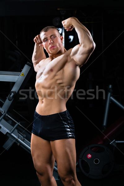 Bodybuilder posing in Gym Stock photo © Kzenon