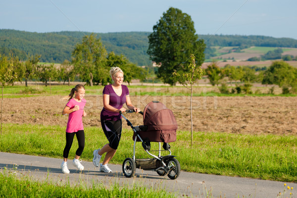 Family sport - jogging with baby stroller Stock photo © Kzenon
