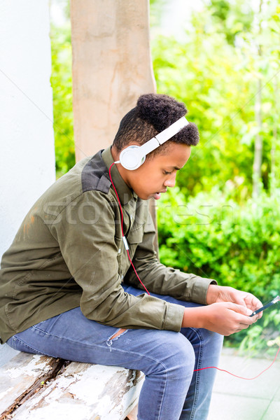 Black boy listening to music with headphones Stock photo © Kzenon
