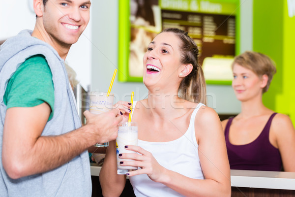 People drinking protein shakes in fitness gym Stock photo © Kzenon