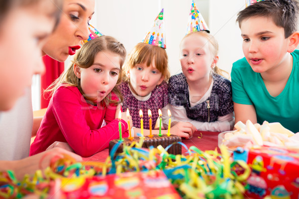 Child on birthday party blowing candles on cake Stock photo © Kzenon