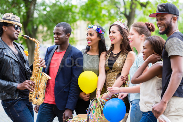 Street artist playing saxophone for multi-ethnic party group  Stock photo © Kzenon