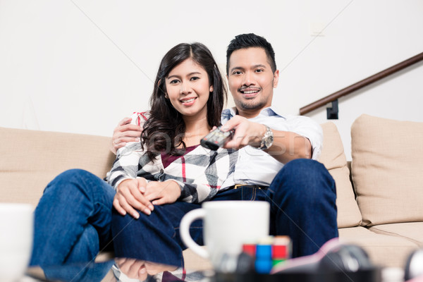 Asian couple on sofa in living room changing tv channel Stock photo © Kzenon