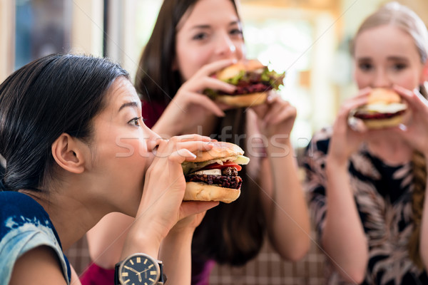 Portrait trois jeunes femmes manger regarder Photo stock © Kzenon