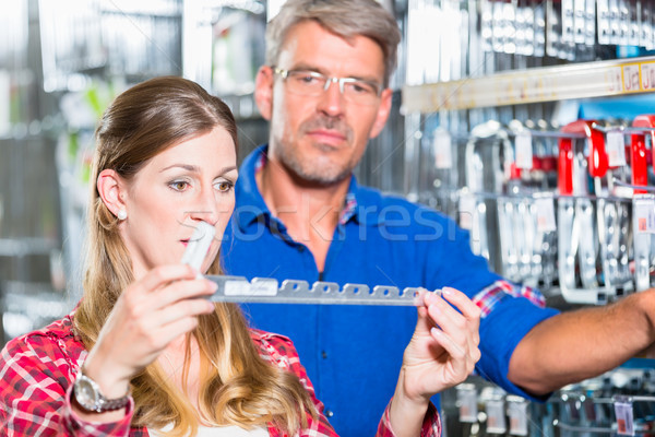 Employee of hardware store helping customer in ironware departme Stock photo © Kzenon