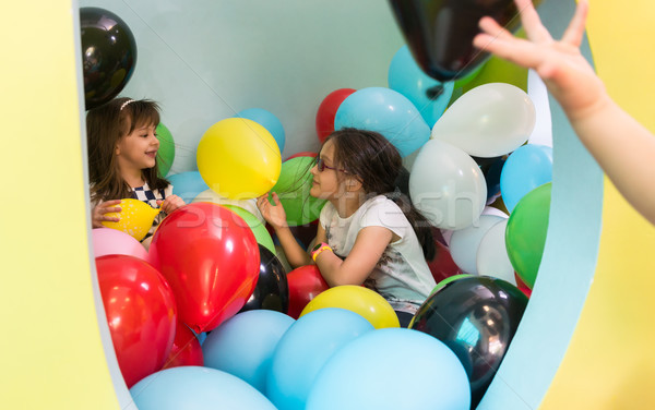 Two cute girls talking while playing with multicolored balloons  Stock photo © Kzenon