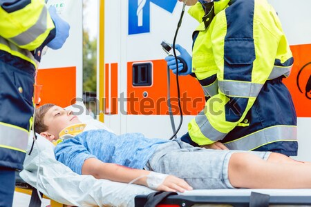 Paramedics measuring blood pressure of injured boy Stock photo © Kzenon
