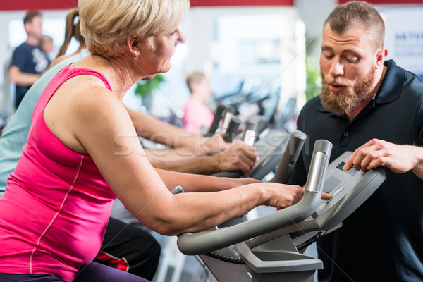 Personal trainer instructs senior woman about spinning at the gy Stock photo © Kzenon