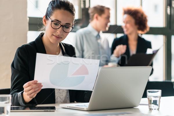 Hard-working young woman analyzing business information Stock photo © Kzenon