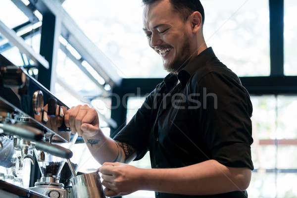 Young cheerful barista preparing coffee at an automatic machine  Stock photo © Kzenon